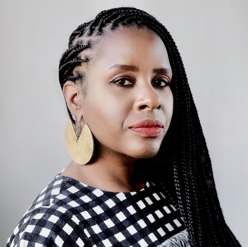 woman in checkered blouse wearing braids and large circular gold earrings