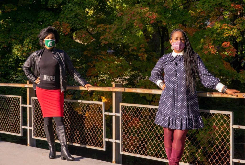 two women standing on a bridge wearing masks