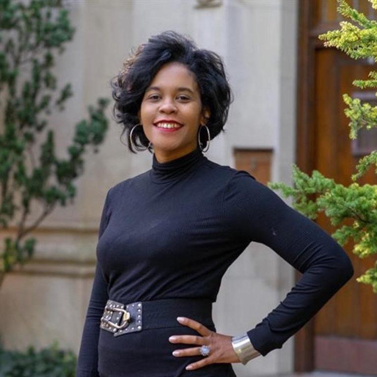 a woman with short dark hair wearing a black long sleeve turtleneck with hoop earrings